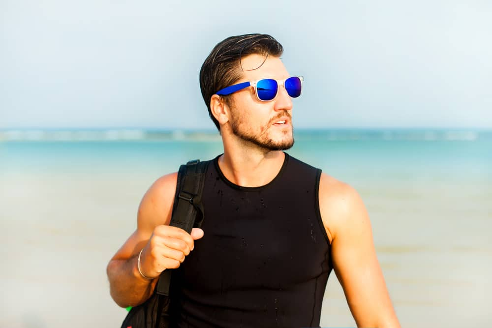 A man carrying a backpack and wearing blue mirrored sunglasses