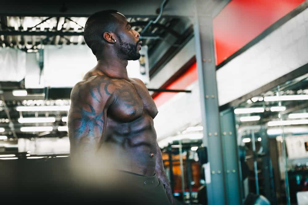 man with abs stands in a gym, looking at his reflection