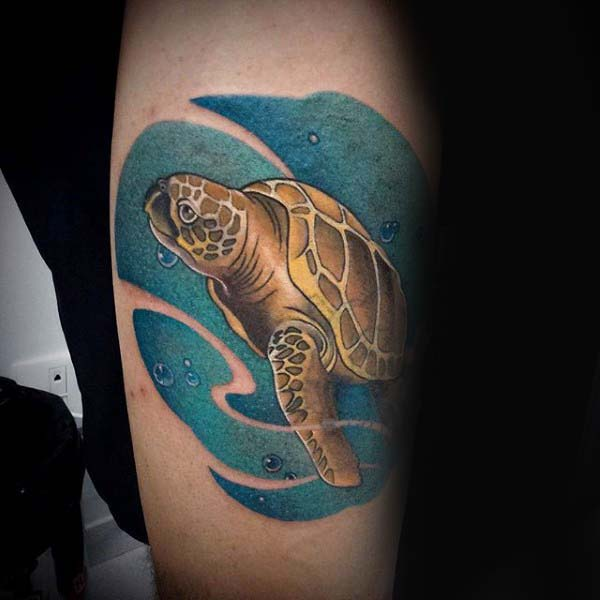 Man With Arm Tattoo Of Swimming Turtle In Blue Ink Water With Negative Space Waves