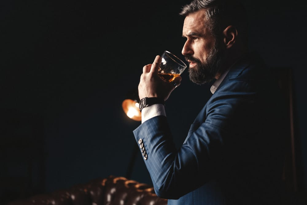 man with beard holding glass of whiskey