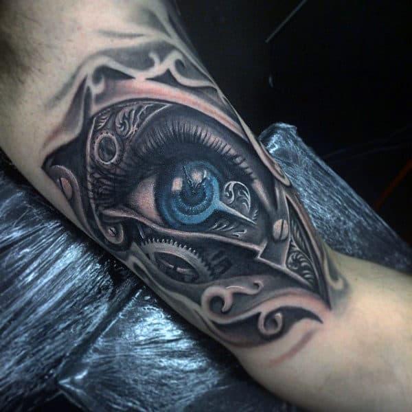 Man With Bicep Steampunk Styled Blue Eye Tattoo Design
