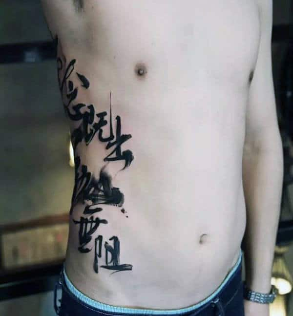 Man With Black Ink Chinese Paint Brush Stroke Writing Text Tattoo On Ribs