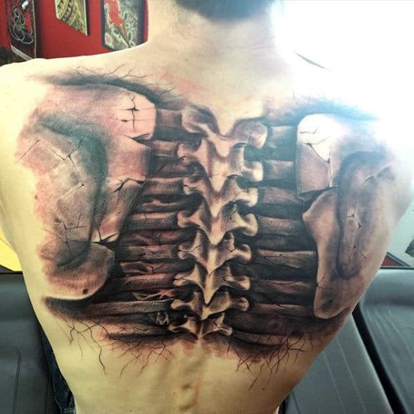 Man With Black Ink Shaded Realistic Spine Tattoo On Back