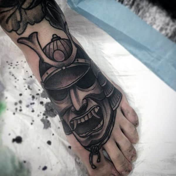 Man With Black Shaded Samurai Mask Foot Tattoo