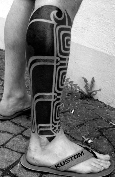 Man With Blackwork Tribal Leg Tattoo Negative Space Design