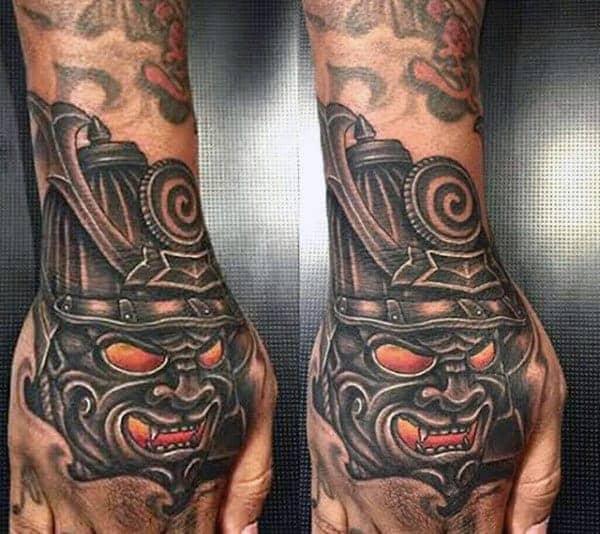 man-with-bold-samurai-mask-hand-tattoo