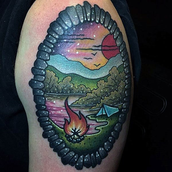 Man With Bordered Upper Arm Tattoo Of Campsite By Lake