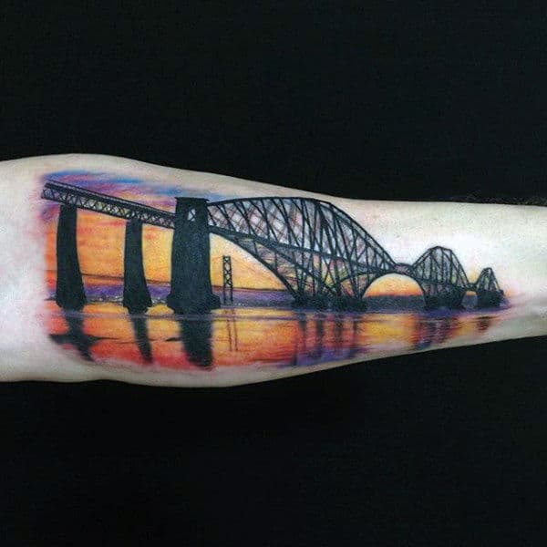 Man With Bridge Over Reflective Sunset Water Tattoo On Forearm