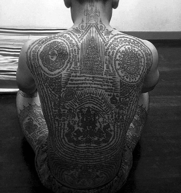 Man With Buddhist Scriptures And Symbols Tattoo On Full Back And Thighs