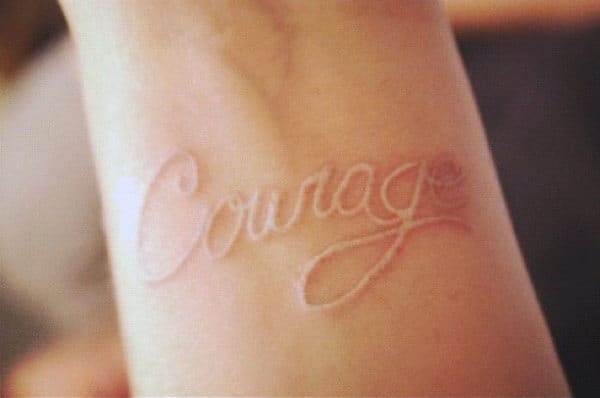 Man With Courage White Ink Lettering Tattoo On Wrist