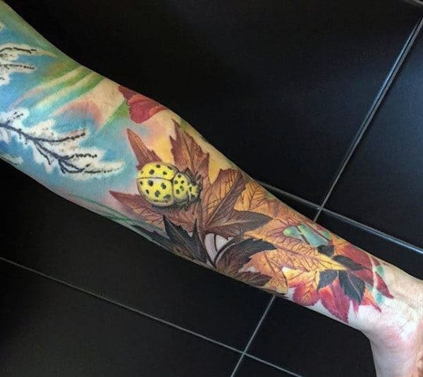 Man With Fall Color Ladybuf On Leaf Full Sleeve Tattoo