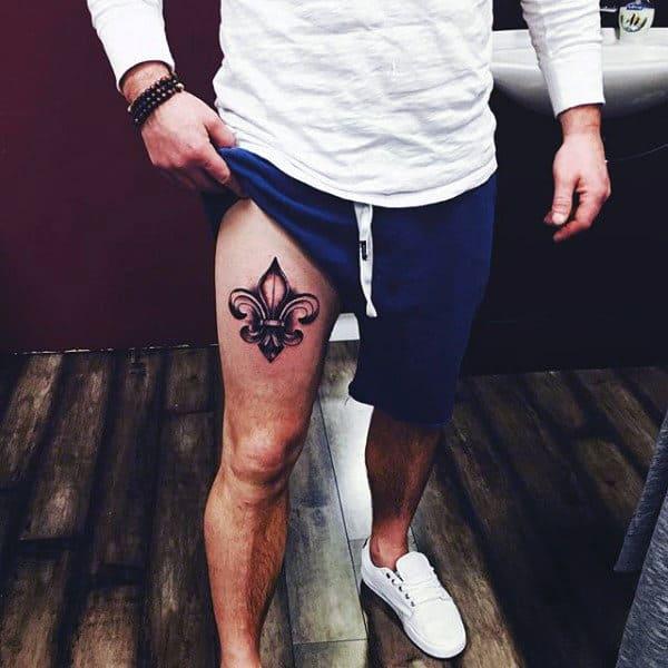 Man With Fleur De Lis Thigh Tattoo