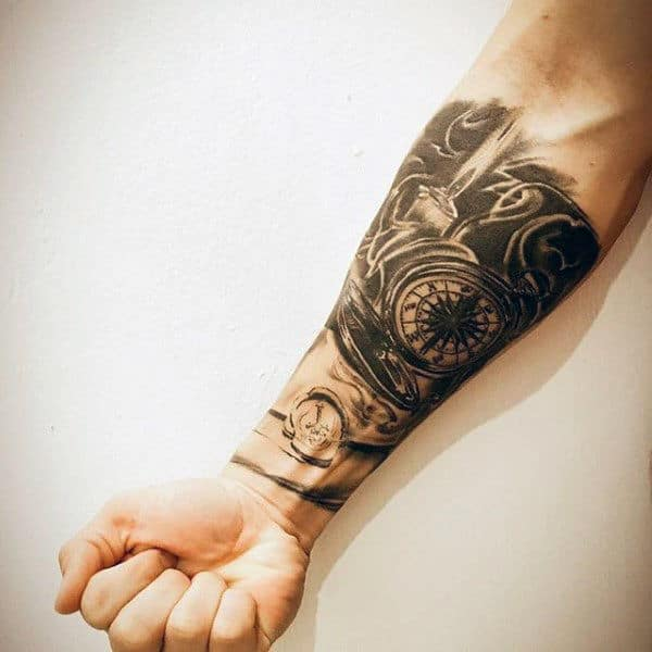 Man With Forearm Sleeve Tattoo Of Compass And Candle Flame