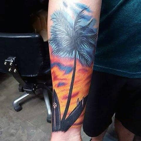 Man With Forearm Sunset Tattoo Including Palm Tree And Surfboards