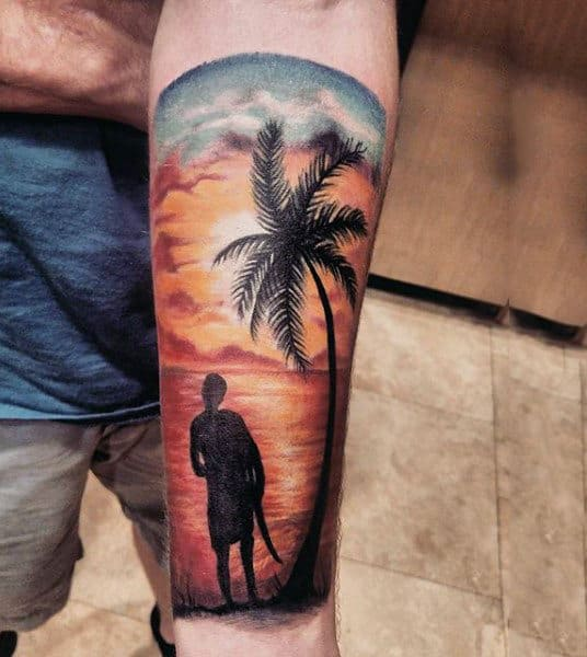 Man With Forearm Tattoo Of Man At Sunset Beach