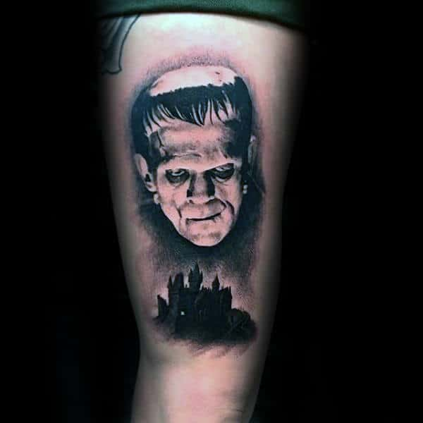 Man With Frankenstein Looking Down On Black Ink Castle Guys Thigh Tattoos
