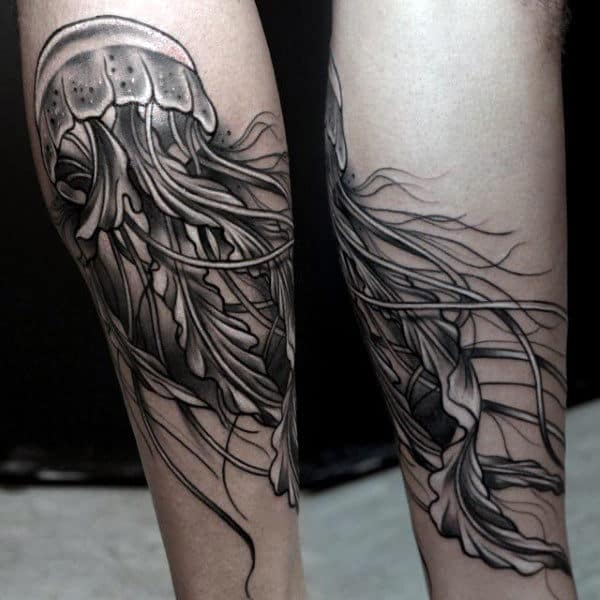 Man With Grey Jelly Fish Tattoo On Lower Legs