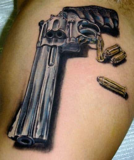 Man With Gun And Bullet Tattoos On Bicep