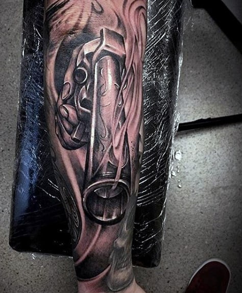Man With Gun Tattoo Of Barrel On Forearm