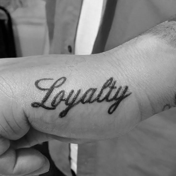 Man With Hand Tattoo Of Loyalty In Cursive Lettering