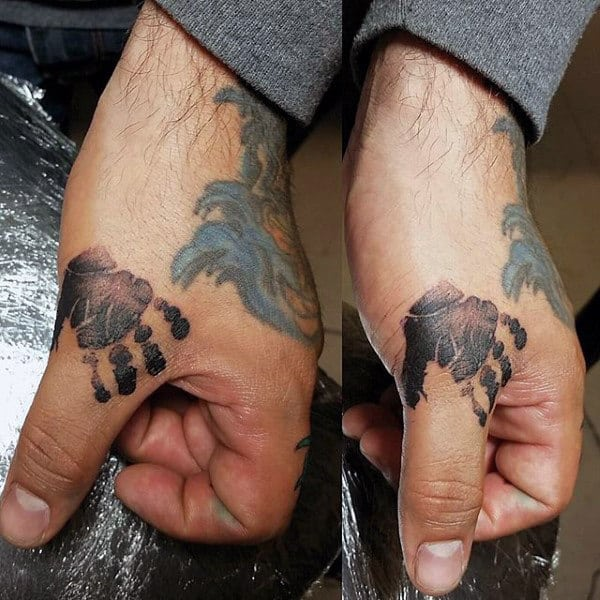 Man With Handprint Tattoo On Thumbs