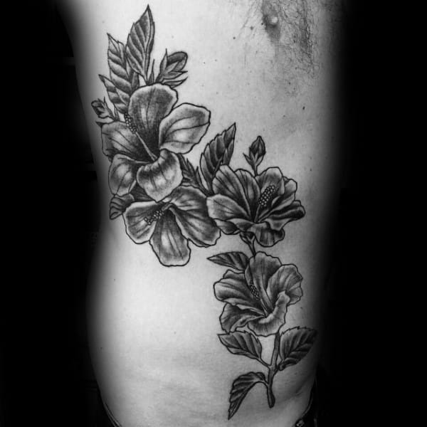 Man With Hibiscus Flowers Tattoo On Rib Cage Side Of Body