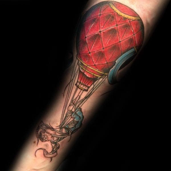 Man With Hot Air Balloon Strings Tattoo On Arm