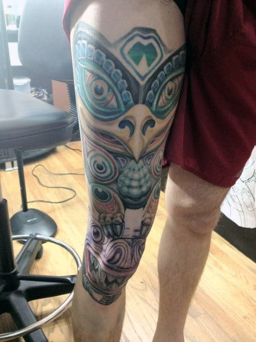 Man With Large Grinning Totem Pole Thigh Piece Tattoo