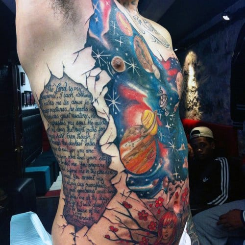 Man With Literary Work And Universe Tattoo On Torso