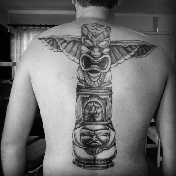 Man With Menacing Totem Pole Black Work Back Tattoo