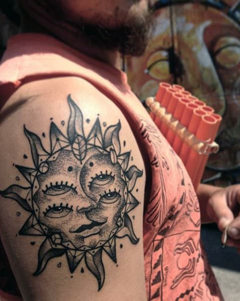 Man With Multiple Eye Sun Tattoo On Upper Arm