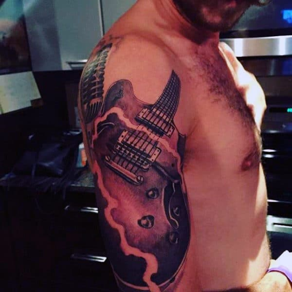 Man With Musical Instrument Tattoo On Arms