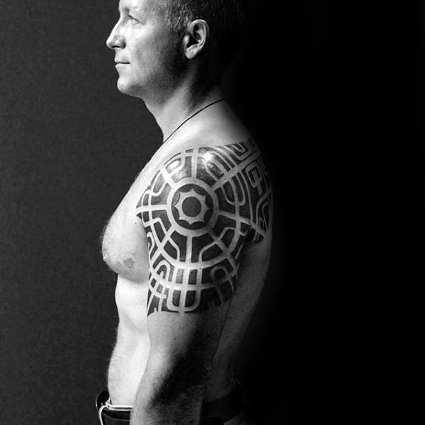 Man With Negative Space Pattern Tribal Arm And Shoulder Tattoo