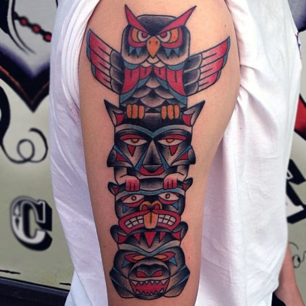 Man With Neo Traditional Style Totem Pole With Owl And Bear On Upper Arm Tattoo