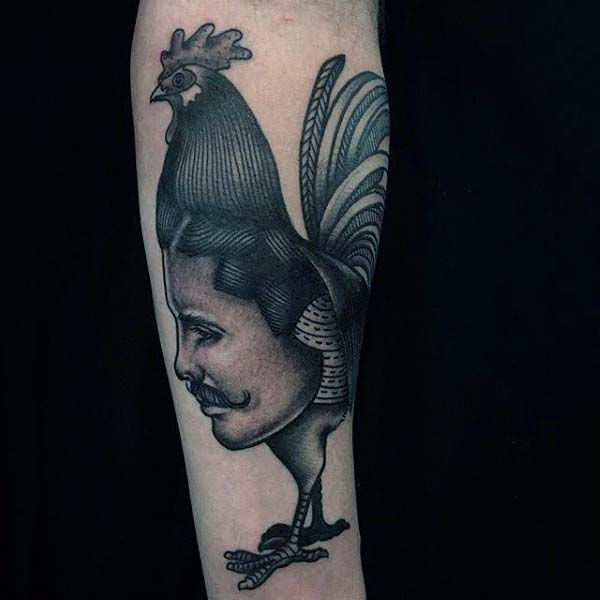 Man With Rooster And Face Tattoo On Forearm In Blackwork