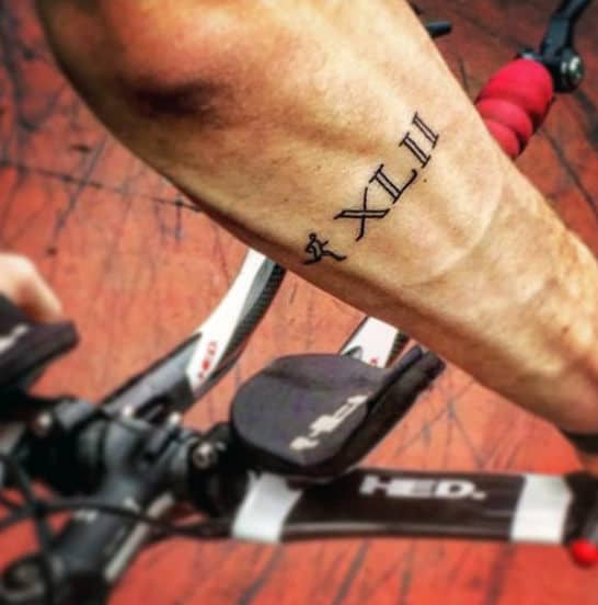 Man With Running Roman Numeral Outer Forearm Tattoo