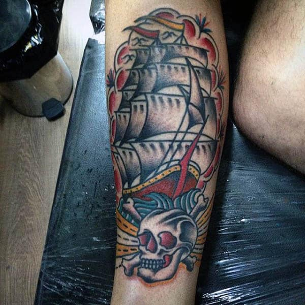 Man With Sailor Jerry Themed Sailboat And Skull Tattoo On Inner Forearm