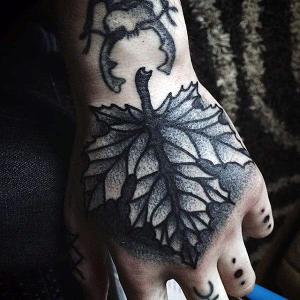 Man With Shaded Autumn Leaf Hand Tattoo In Black Ink