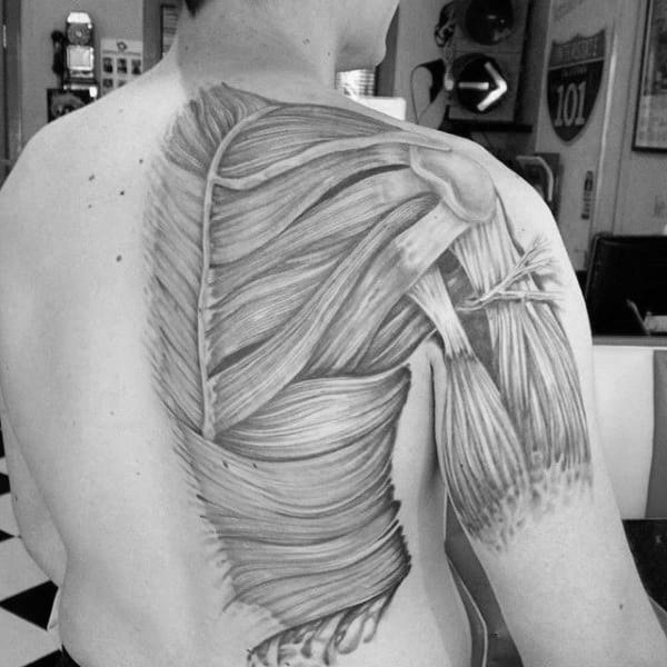 Man With Shaded Black And Grey Muscle Back Tattoo