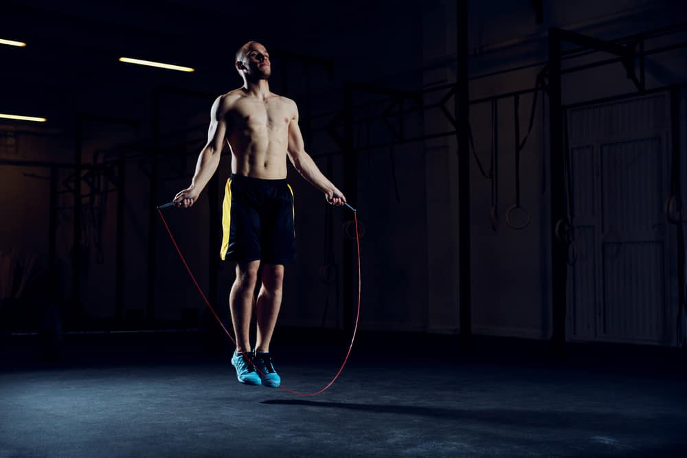 athletic young man training with skipping rope