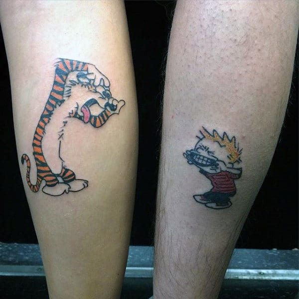 Man With Small Calvin And Hobbes Tattoos On Back Of Legs
