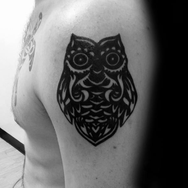 Man With Small Dark Black Ink Tribal Owl Upper Arm Tattoo