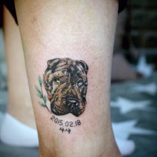 Man With Small Dog Face Tattoo On Leg