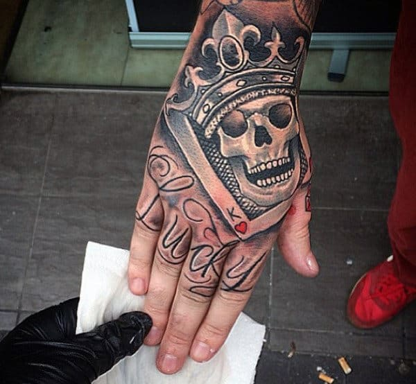 Man With Smiling Skull And Crown Tattoo On Hands