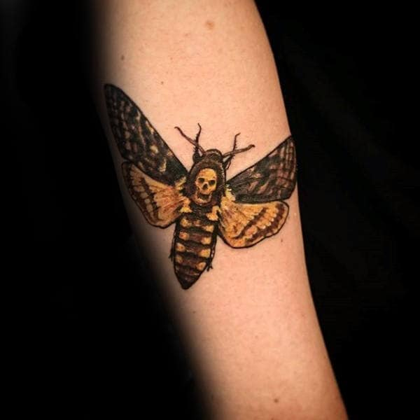 Man With Tattoo Of Black And Yellow Moth On Forearm