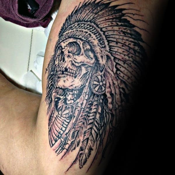 Man With Tattoo Of Indian Skull On Outer Arm Bicep