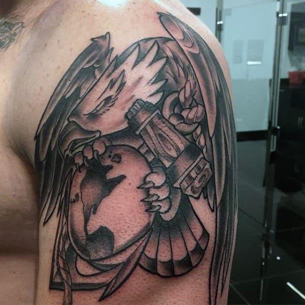 Man With Tattoo Of Marine Logo On Upper Arm
