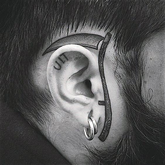 Man With Tattoo Of Scythe Around Ear On Face