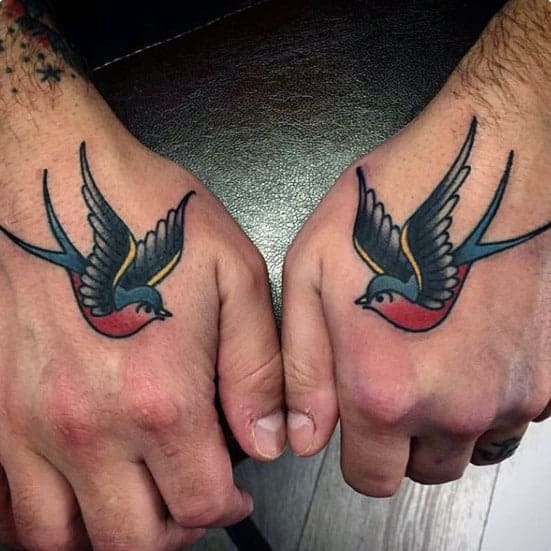 man-with-traditional-swallow-tattoos-on-hands