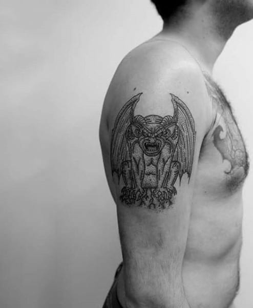 Man With Upper Arm Tattoo Of Gargoyle Design